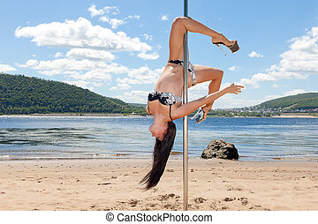 dancer on pole upside down background of summer beach and blue sky