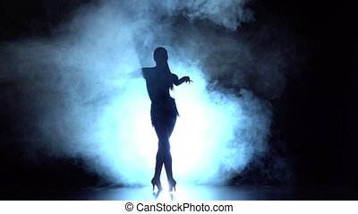Dancer performs latin dance in the studio, silhouette. Slow motion