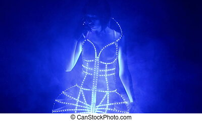 Dancer poses in led costume dress in smoke on stage