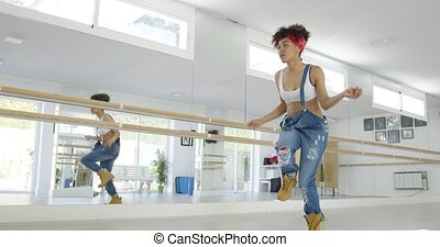 Dancer steps forward and snaps finger in studio as she...