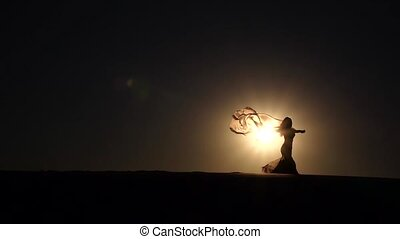 Dancer with a veil in her hands dancing belly dance on the beach. Silhouette. Slow motion
