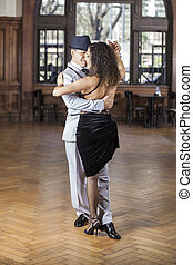 Dancers Performing Tango On Hardwood Floor In Restaurant