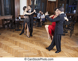 Dancers Performing Tango On Hardwood Floor While Couple Dating