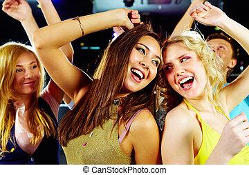 Dancing at party - Two joyful girls dancing in night club...