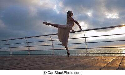Dancing ballerina in beige silk dress and pointe on...