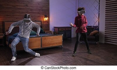 Happy diverse friends using futuristic VR headsets while dancing in domestic room during immersion in cyberspace. Modern mixed race teens having fun performing dance in augmented-reality goggles
