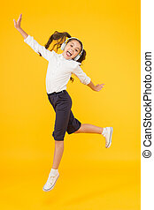 Dancing class. Small dancer moving to music on yellow background. Little child enjoy dancing to modern music. Energetic kid dancing with pleasure. Learning in dancing school