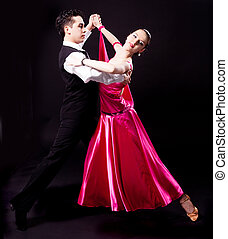 dancing couple - a couple dancing against black studio...