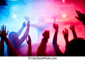 Dancing crowd - Male deejay in front of dancing crowd