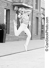 Dancing cutie. Adorable dancer moving to music on city street. Small child enjoy dancing to modern music. Energetic little girl dancing with pleasure. Listening dancing music