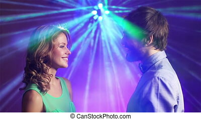 Side view of smiling young people dating and dancing in the club