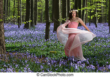 Dancing fairy in bluebells forest