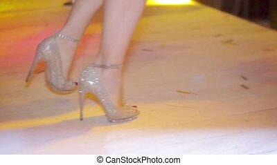 Dancing feet of go go dancer on high heels in nightclub. Red tippet. Slow motion