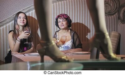 Dancing feet on table, girl and woman at table and look on...