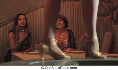 Dancing feet on table. Watching girl, woman at table on...