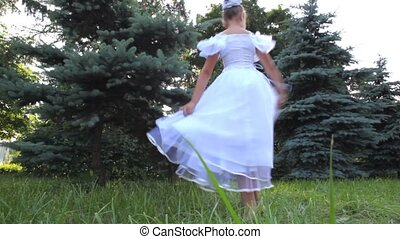 dancing girl in white dress is turned on grass