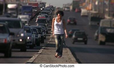 dancing girl walks on highway middle in city - dancing girl...