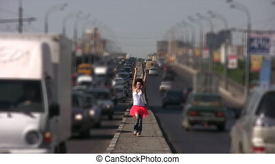 dancing girl walks on highway middle in city