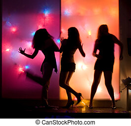 Dancing girls silhouettes in front of colorful disco lights