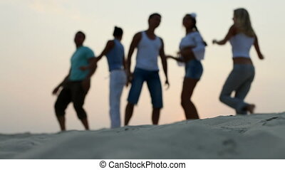Dancing group - A group of young people dancing on the beach...