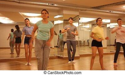 Dancing group of five teenagers practicing new dance in studio