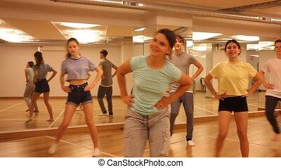 Dancing group of five teenagers practicing polka dance in studio