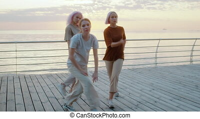 Dancing group of young talented freak women performing freestyle hip-hop moves. Girls enjoying modern dance expression. Outdoor training near sea or ocean during sunset.