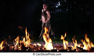 Dancing in Fire - Young Caucasian woman dancing in the night...