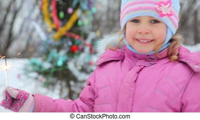Dancing little girl with sparkler against christmas tree