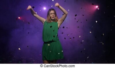Dancing of young woman in green dress, under falling confetti