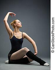 Dancing on the wooden floor ballet dancer with her hand up