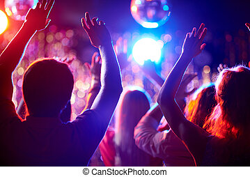 Dancing people - Crowd of people with raised arms dancing in...