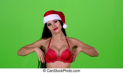 Dancing santa woman in a brilliant swimsuit moves in time with the music. Green screen. Slow motion