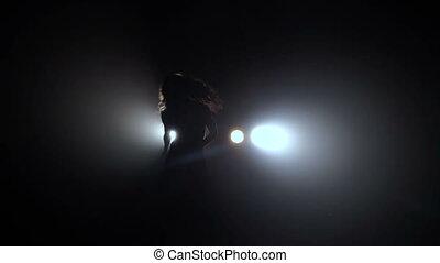 Dancing silhouette in black studio