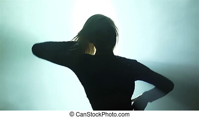 Silhouette of a young woman dancing in the club against the light