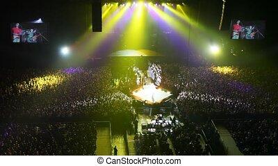 dancing singer on scene among spectators in concert hall