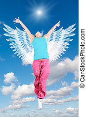 dancing woman angel with wings in sportswear jumps on sky collage