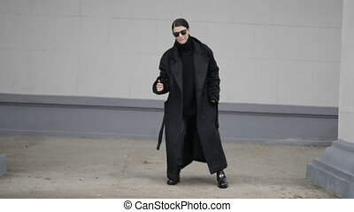 Dancing woman in black coat