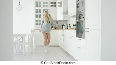 Dancing woman in kitchen - Young happy girl wearing home...