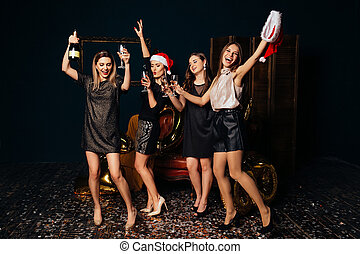 Dancing women with champagne at Christmas party
