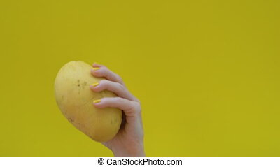 Dancing yellow mango on a yellow background in a woman's...