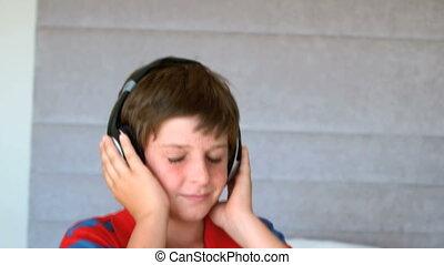 Dancing young boy enjoying music wi