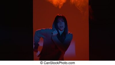 Dancing young girl performing freestyle dance in colourful light in studio with smoke. Modern lifestyle, rap and hiphop. High quality 4k footage