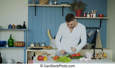 Dancing young man cooking vegetarian breakfast cutting vegetables for salad in kitchen at home