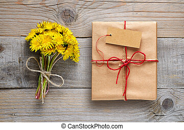 Dandelion flowers and gift box with tag on wooden background