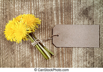 Dandelion flowers with paper tag