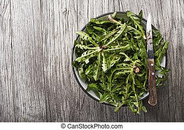 Dandelion - Fresh dandelion leaves on wooden background...