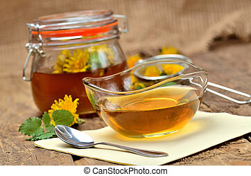 Dandelion honey in glass, spoon, dandelion head around, small colander and full jar in background