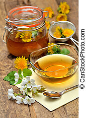 Dandelion honey, spring flowers, spoon, dandelion head around, small colander and full jar in background - vertical photo