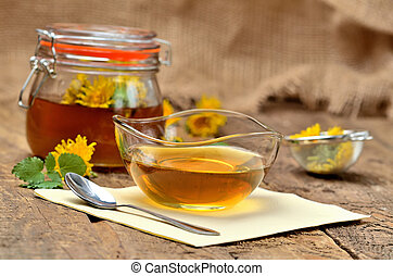 Dandelion jam in glass, spoon, dandelion head around, small colander and full jar of jam in background